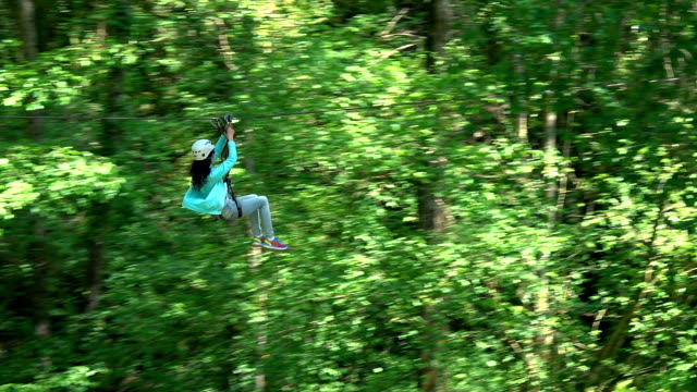 happy brunette woman sliding down a zip line - ロープスライダー点の映像素材/bロール