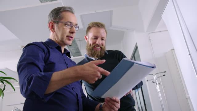 glückliche geschäftskollegen diskutieren papierkram - leitende position stock-videos und b-roll-filmmaterial