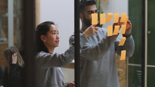 Happy business colleagues sticking adhesive notes on glass wall while working in office