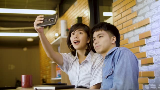 Happy business couple or student taking selfie together at working space or modern office