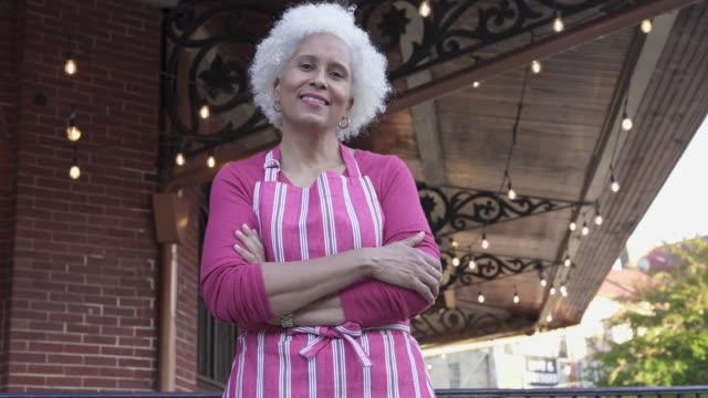 stockvideo's en b-roll-footage met happy business owner in front of her restaurant - straatnaambord