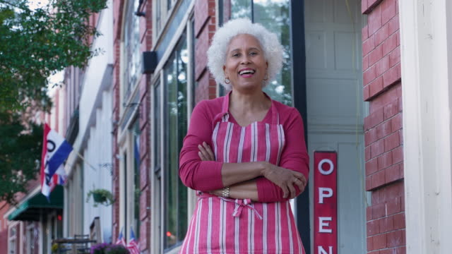 happy business owner in front of her store - street name sign stock videos & royalty-free footage