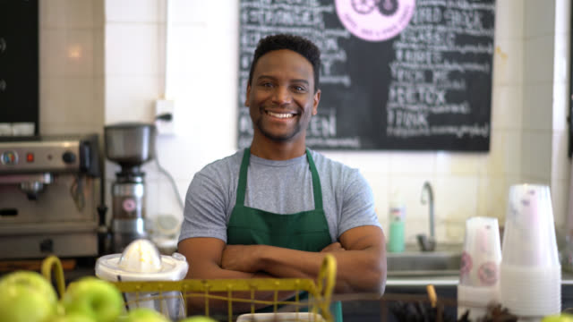 Happy business owner of a juice bar looking at camera smiling with arms crossed