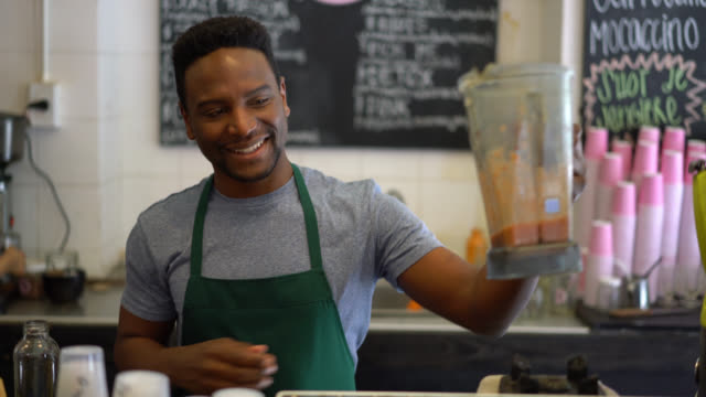 Happy business owner of a juice bar making a juice and serving it in a bottle with a straw