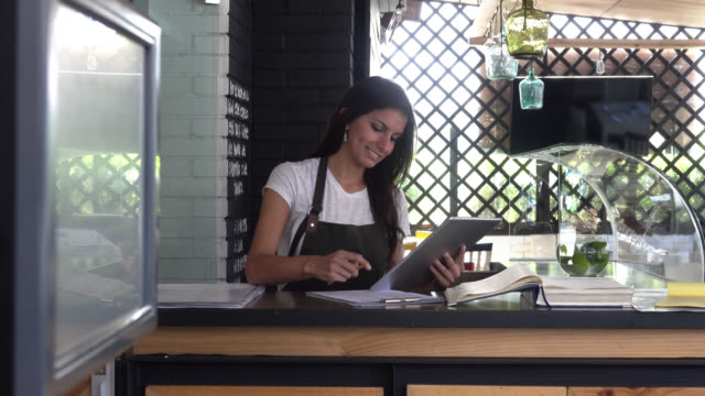 Happy business owner using a tablet computer doing the books