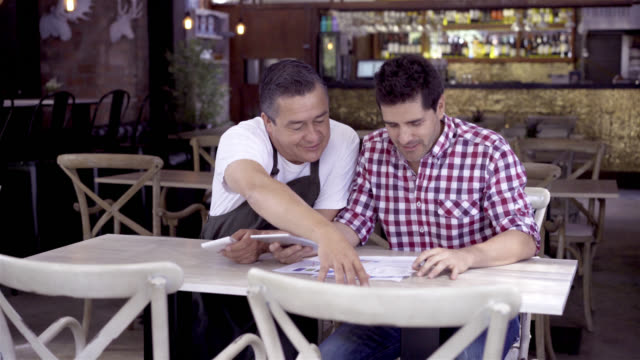 Happy business owner with the restaurant administrator doing the books while holding his tablet
