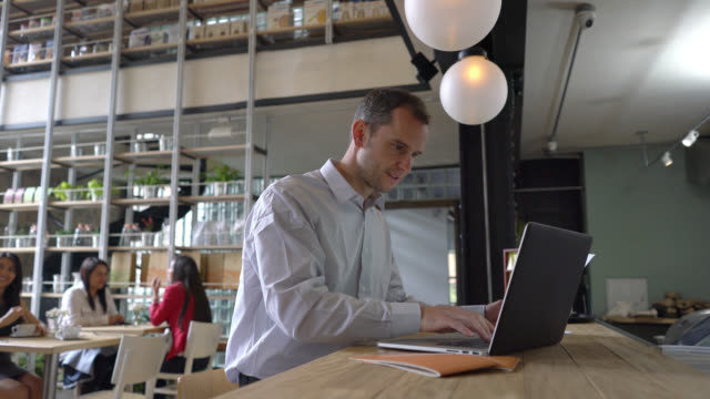 happy business owner working on his laptop on the counter - owner stock videos & royalty-free footage