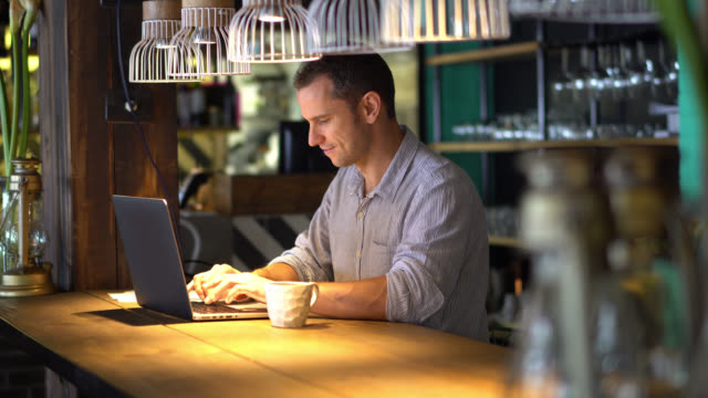 happy business owner working on his laptop - cafe stock videos & royalty-free footage