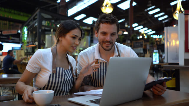 happy business owners of a restaurant doing the books using a laptop and paperwork- - business plan stock videos & royalty-free footage