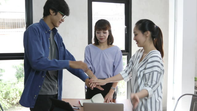 Happy business-Leute klatschen mit Arme heben in celebration Gruppe bilden