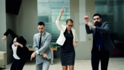 Happy business team men and women are dancing at work party together moving bodies, laughing and singing relaxing in hall. Coworkers, relaxation and emotions concept.