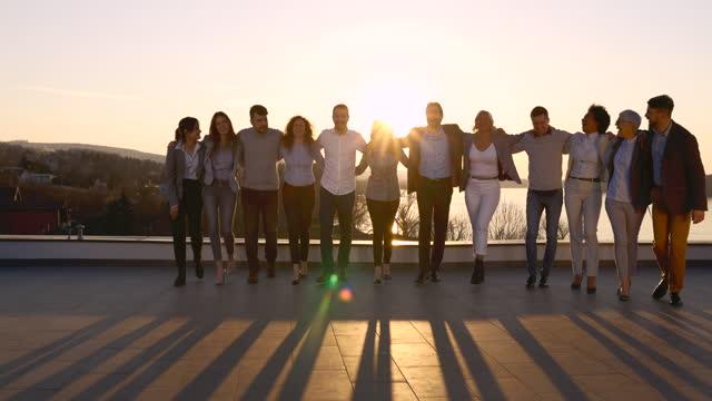 glückliches business-team zu fuß umarmt auf einem dach bei sonnenuntergang. - gemischte altersgruppe stock-videos und b-roll-filmmaterial