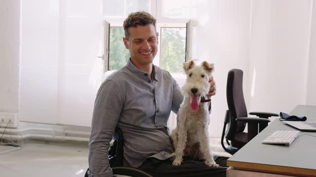 stockvideo's en b-roll-footage met gelukkige zakenman bij bureau met hond - alleen één mid volwassen man