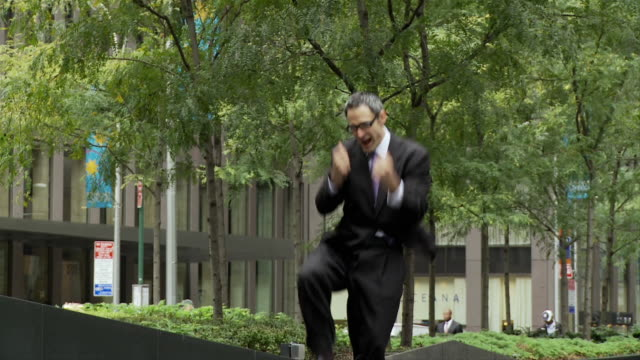 slo mo ws happy businessman cheering and jumping outdoors / new york city, new york, usa - satisfaction stock videos and b-roll footage