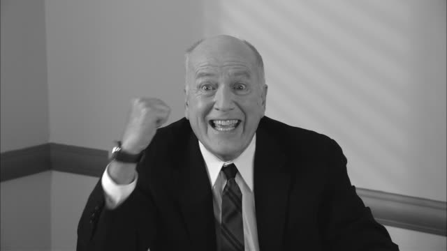 b/w ms happy businessman clapping  giving thumbs up  shaking fists  smiling at camera  leaning back and putting feet up/ new york city - feet up stock videos & royalty-free footage