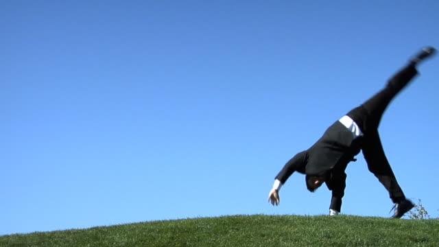 slo mo, ws, happy businessman doing cartwheel in field - ganzkörperansicht stock-videos und b-roll-filmmaterial