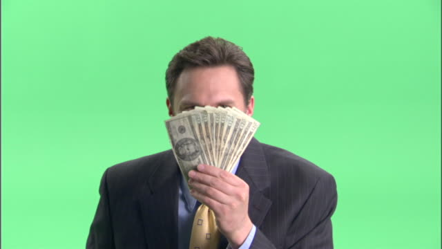 cu, happy businessman holding fan of american dollar banknotes in front of face in studio, portrait - corruption stock videos and b-roll footage
