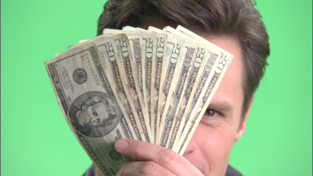 ecu, happy businessman holding fan of american dollar banknotes in front of face in studio, portrait - corruption stock videos and b-roll footage