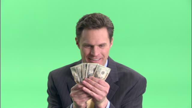 vídeos de stock, filmes e b-roll de cu, happy businessman holding fan of american dollar banknotes in studio, portrait - só um adulto de idade mediana