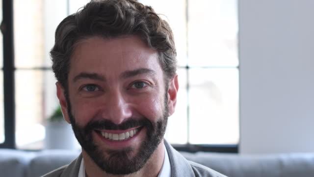 glücklich kaufmann in seinen 40ern mit bart und dunklen haaren lächelnd in richtung kamera - braunes haar stock-videos und b-roll-filmmaterial