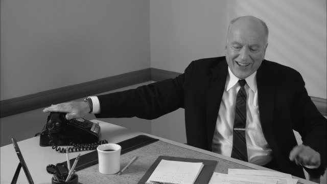 b/w ms happy businessman in office on phone call/ man hanging up phone  leaning back in chair  and giving thumbs up/ new york city - hanging up stock videos & royalty-free footage