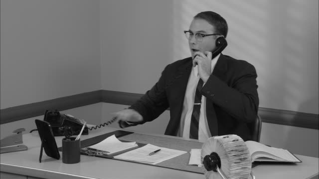 b/w ms happy businessman in office on phone call/ man hanging up phone  leaning back in chair  and looking pleased/ new york city - hanging up stock videos and b-roll footage