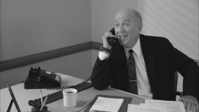 b/w ms happy businessman in office on phone call/ man hanging up phone  giving thumbs up and drinking coffee/ new york city - hanging up stock videos & royalty-free footage