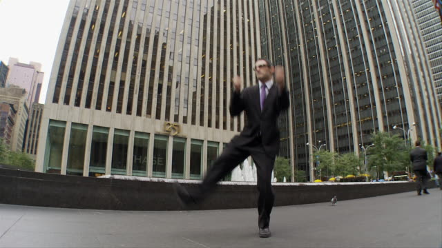 SLO MO WS Happy businessman jumping outdoors / New York City, New York, USA