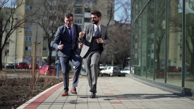 vidéos et rushes de hommes d'affaires heureux dansant dans la rue et célébrant leurs promotions - collègue