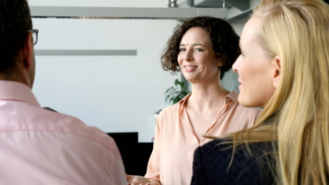 Happy businesswoman brainstorming mature coworkers