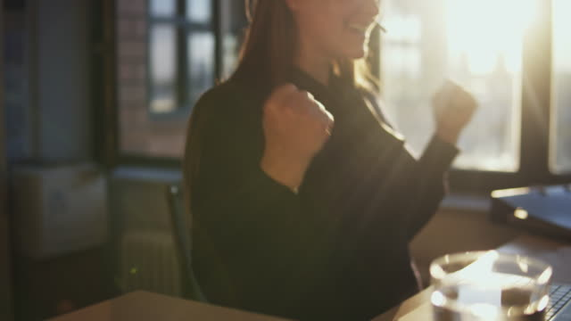 happy businesswoman clenching her fist in office. - success stock-videos und b-roll-filmmaterial