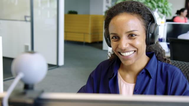 stockvideo's en b-roll-footage met gelukkige zakenvrouw met een video-oproep in office - looking at camera