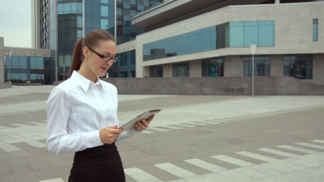 happy businesswoman in glasses talking on the tablet and laughs - orthographic symbol stock videos and b-roll footage
