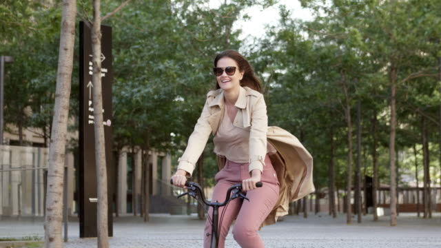 happy businesswoman riding bicycle in downtown - fare una pausa video stock e b–roll