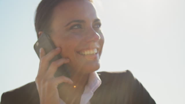 happy businesswoman talking on phone against sky - entrepreneur stock videos & royalty-free footage