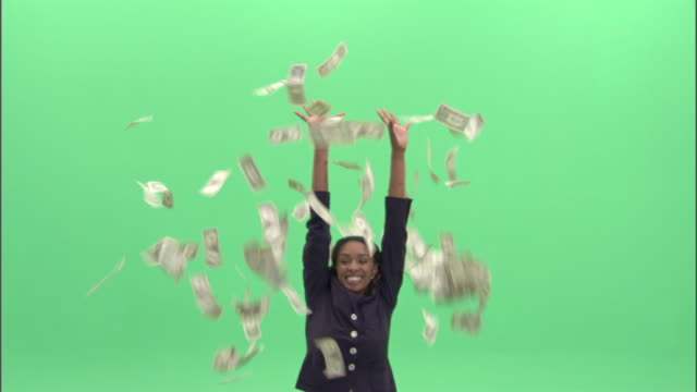 MS, Happy businesswoman throwing American dollar banknotes in studio