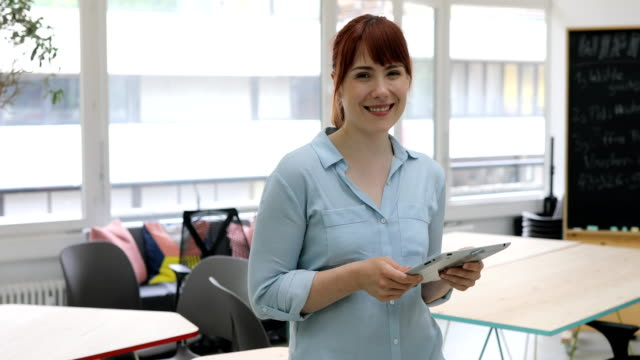 Happy businesswoman with digital tablet in office