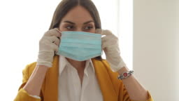 Happy businesswoman with protective face mask and surgical gloves
