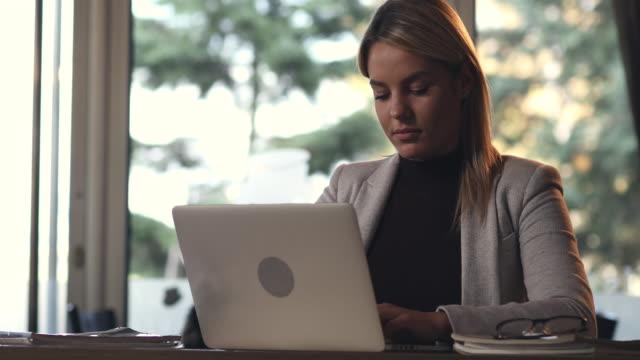 Glücklich Geschäftsfrau Schreiben einer E-mail auf einem Laptop und ans Telefon.