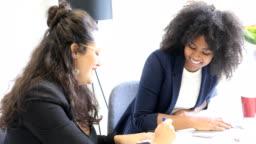 Happy businesswomen discussing in start up office