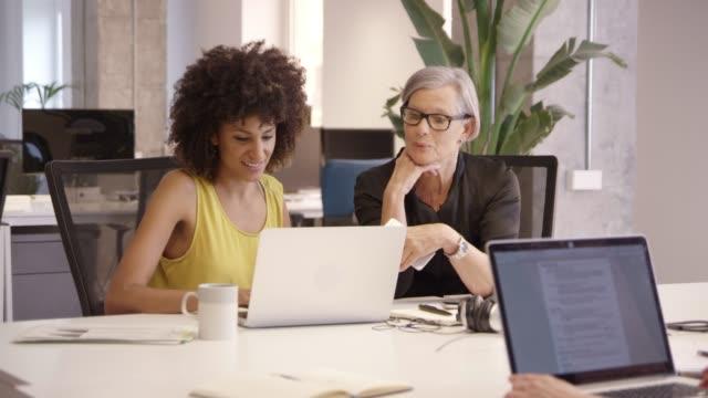 stockvideo's en b-roll-footage met gelukkig zakenvrouwen bespreken over laptop aan balie - mid volwassen vrouw