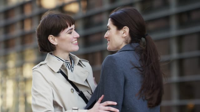 happy businesswomen embracing and talking in city - colleague hug stock videos & royalty-free footage
