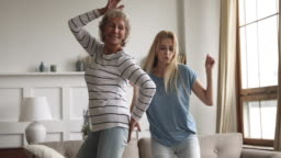 Happy carefree young daughter and old mother dancing at home