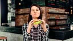Happy casual European female eating appetizing juicy burger at fast food restaurant medium shot