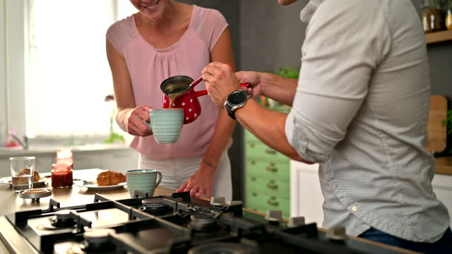 happy caucasian couple having coffee and breakfast at home - mid adult couple stock videos & royalty-free footage