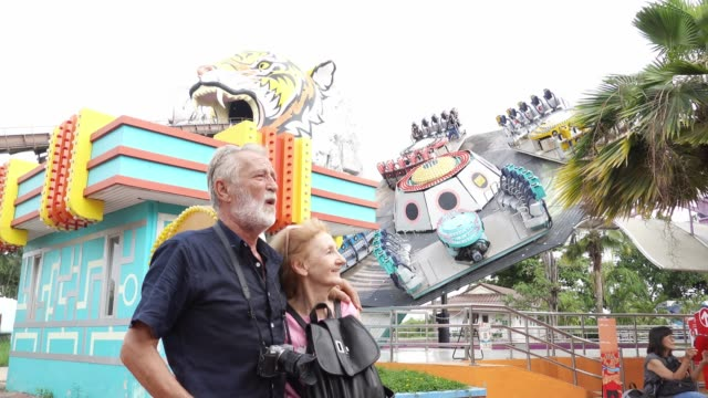 happy caucasian elderly couple  at an amusement park - 60 64 years stock videos & royalty-free footage