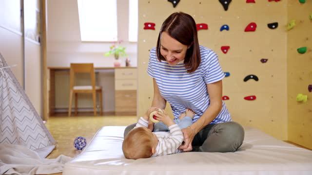 vídeos y material grabado en eventos de stock de feliz madre caucásica jugando con el niño en la sala de juegos en casa - artículo de montañismo