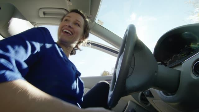 彼女の30代の幸せな白人女性は運転席側の車のドアを開き、中に入れ、点火のキーを置き、彼女のシートベルトをバックル、そして晴れた日に乗客の座席の誰かにåtalks ます - 車のキー点の映像素材/bロール