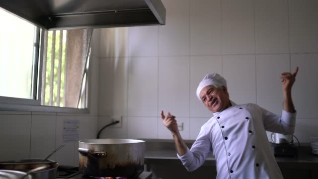 happy chef dancing while cooking in a commercial kitchen - good news stock videos & royalty-free footage