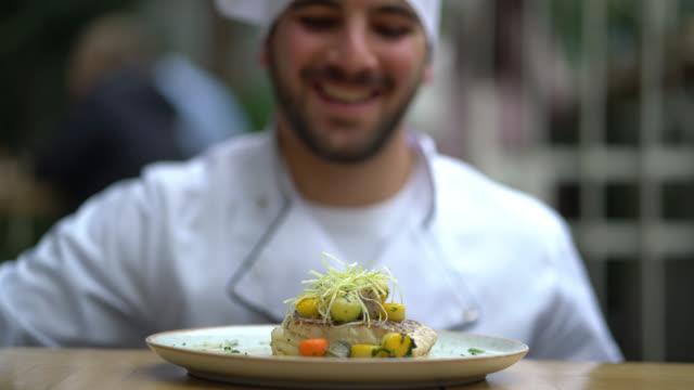 chef felice che decora un piatto di cibo in un ristorante - arrangiare video stock e b–roll